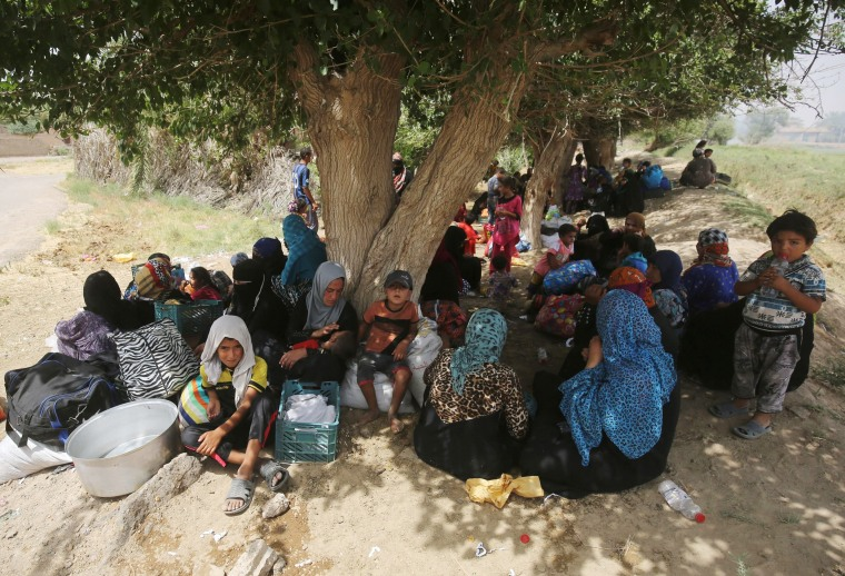 Image: Displaced Iraqis wait to receive food and aid at the village of al-Azraqiyah
