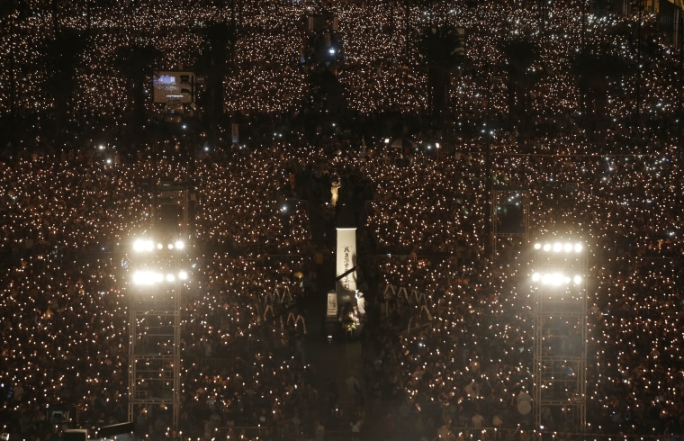 Image: Tens of thousands of people attend a candlelight vigil at Victoria Park in Hong Kong