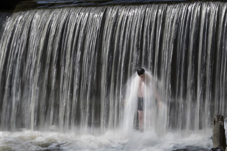Image: A boy cools himself off during a heat wave in Vilnius