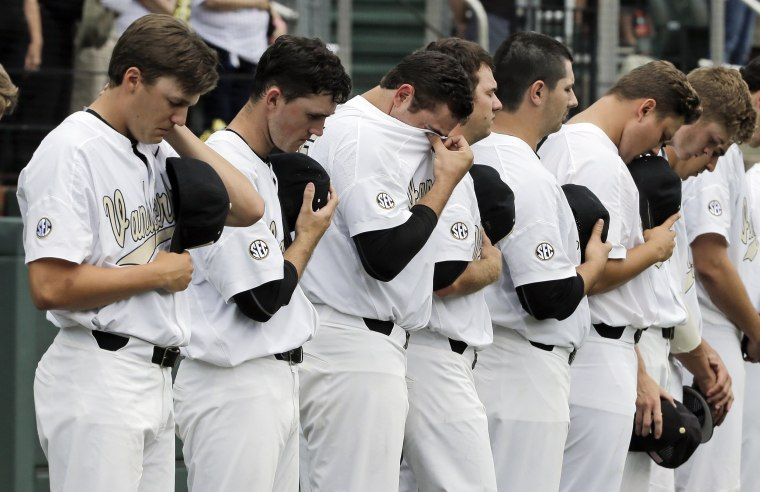 Image: Vanderbilt pitcher Ben Bowden, third from left, wipes his eyes during a moment of silence