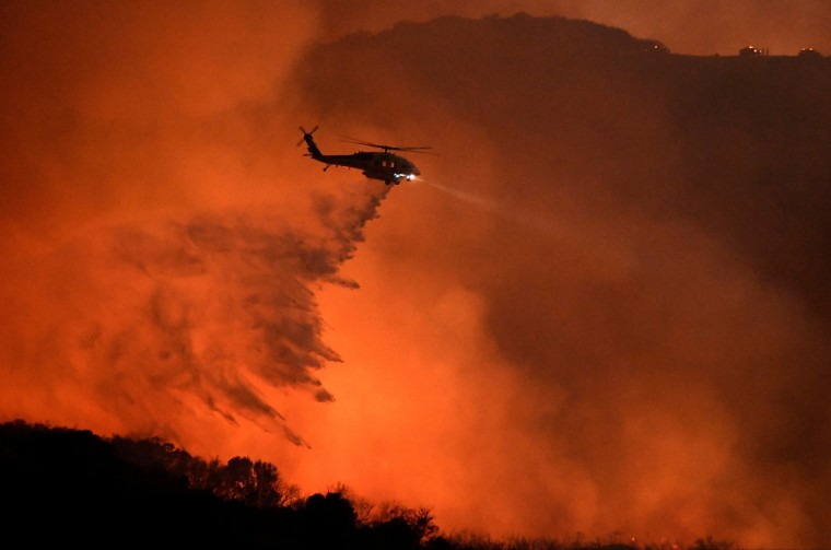 """Image: A helicopter makes a water drop at the """"Old Fire"""", which burned in Calabasas, California"""