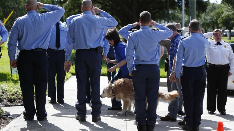 Bretagne the last surviving search and rescue dog from 9/11 is walked by her handler Denise Corliss past a flank of members of the Cy-Fair Volunteer Fire Department