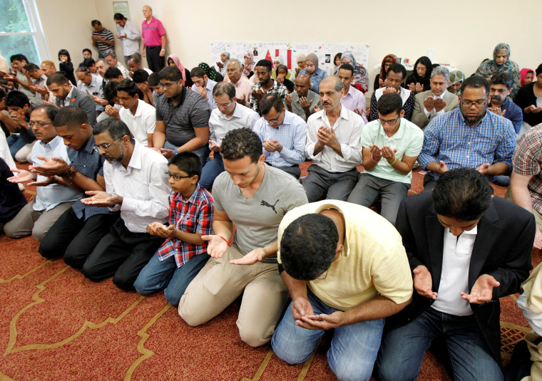 Image: Members of the Louisville Islamic Center pray together before an inter-faith service to honor Muhammad Ali.