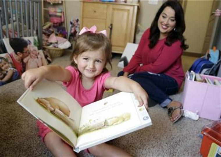 Amanda Evans-Clark reads a book with her daughter, Mira, 2, in Carmel, Ind. The book features voice recordings from her husband, Joe Clark. He died of advanced colon cancer at 31, after a year of chemotherapy and last-ditch major abdominal surgery. The decision to end treatment had a surprise effect on Clark and his wife.