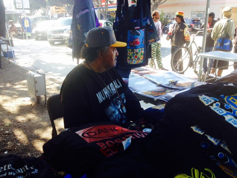 A man wearing a Muhammad Ali shirt watches over a table of merchandise in South Los Angeles.