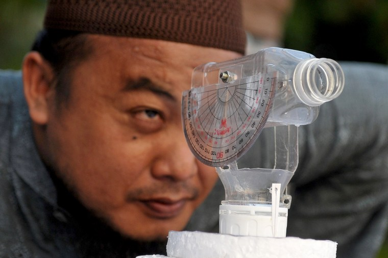 Image: A Muslim man use his made-self tools to look at the position of the moon to check the start of the Muslim holy month of Ramadan at Jerman beach, Kuta