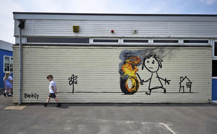 Image: Reception class school children stroll past a mural attributed to Banksy in Bristol
