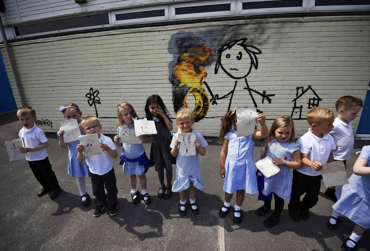 Image: Reception class school children show off their drawings of a mural attributed to Banksy in Bristol