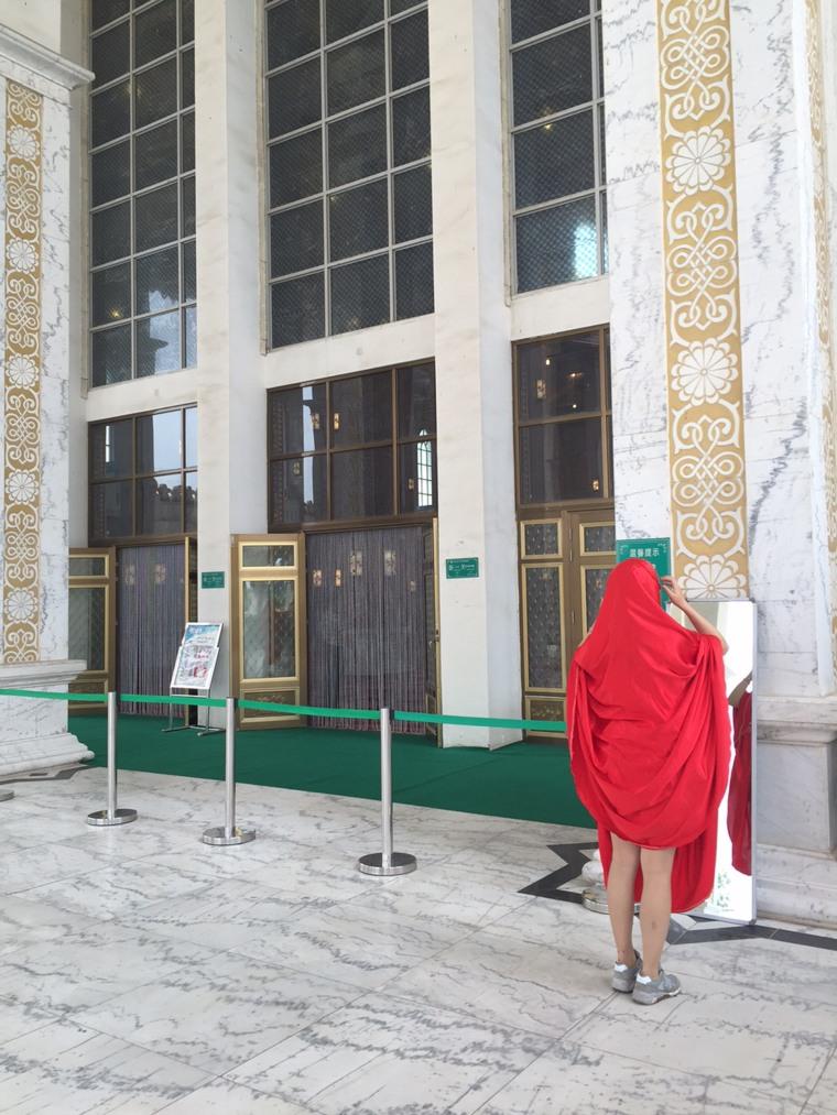 Image: A Chinese tourist adjusts a borrowed abaya at the Golden Palace