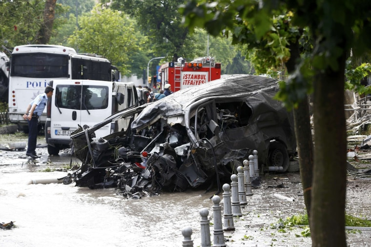 Image: A destroyed van is near a Turkish police bus which was targeted in a bomb attack