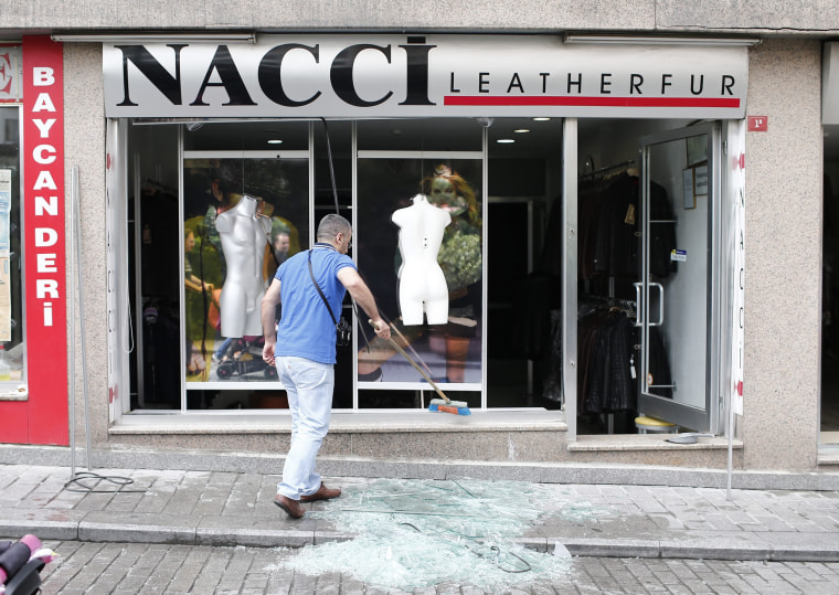 Image: A person removes glass shattered by the blast from the entrance of a shop