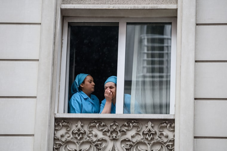 Image: Hotel maids react at a window near the site of the attack