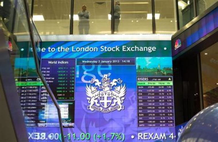 Workers speak above an electronic information board at the London Stock Exchange in the City of London
