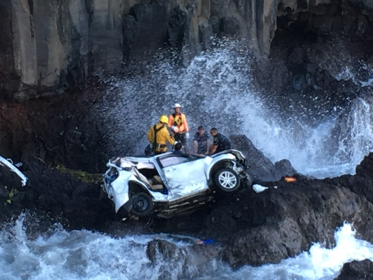 Rescue workers respond to the scene of a car crash off Maui's Hana Highway in Hana, Hawaii. A Maui woman who was driving the vehicle when it plunged off the cliff is charged with murder in the death of her twin, who was in the passenger's seat.