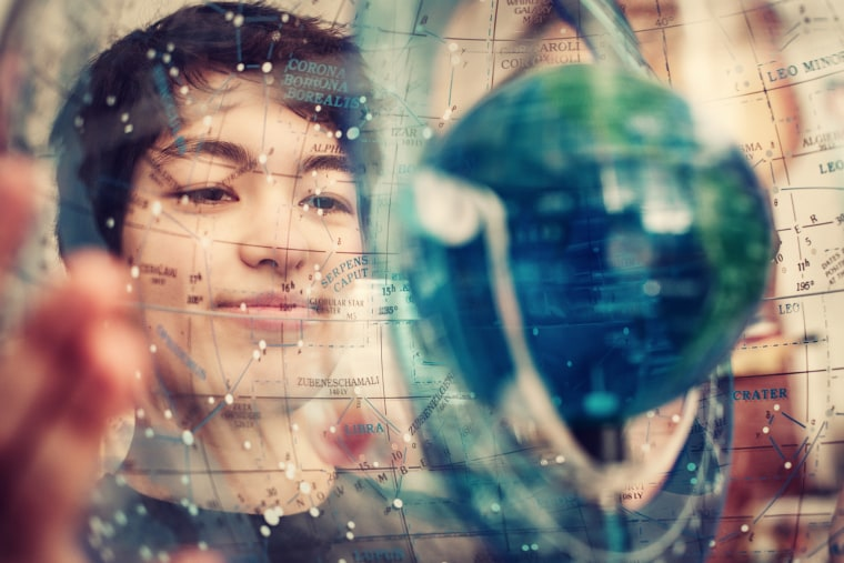 Michelle Kunimoto holds a celestial sphere, showing the stars as they appear in our skies. She has added four new planets to the map of the sky, including a system that might be suitable for life.