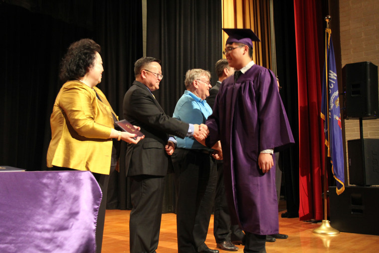 Chris Her-Xiong, the founder and executive director of the school, with graduation speaker Dr. Xa Xiong, and school boardmember Don Cohen congratulating a graduating senior.