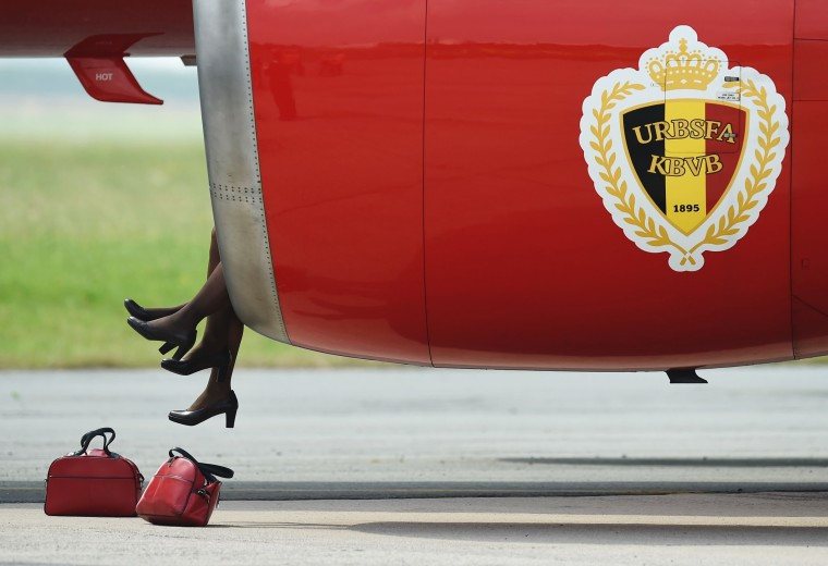 Image: Flight attendants sit in the turbine of Belgium's national football team's plane before take off