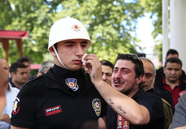 Image: A relative of one of the victims of Tuesday's explosion, wipes the face of a Turkish police officer