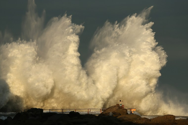 Image: A man watches a wave hit a rock pool at Curl Curl beach