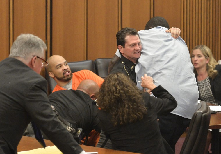 Image: A court officer tackles the father of one of three victims of Ohio serial killer Michael Madison