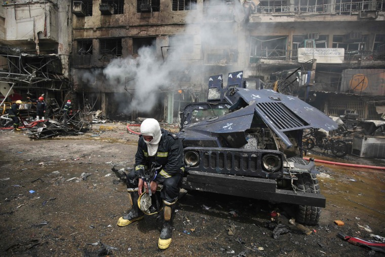 Image: An Iraqi fireman sits after a fire was extinguished at the site of car bomb attack