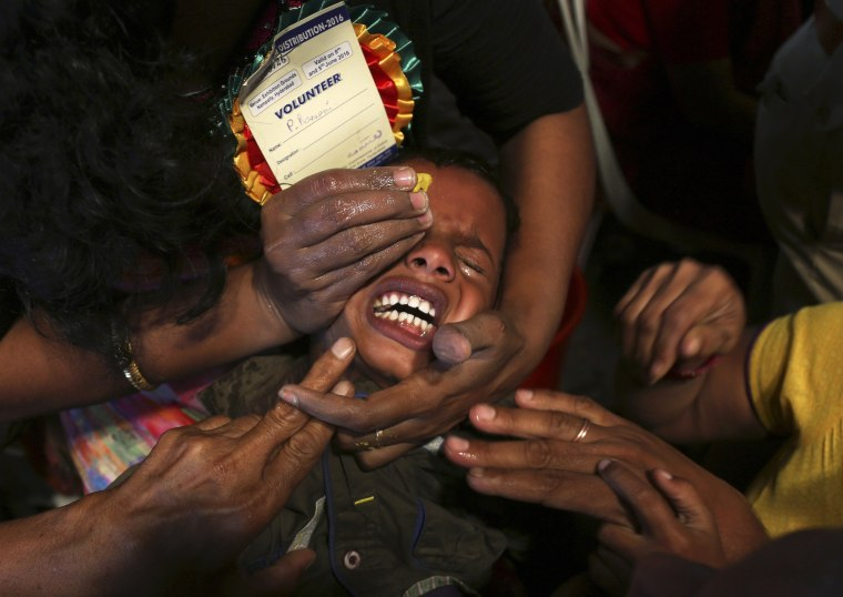 Image: Volunteers try to open the mouth of a child suffering from asthma