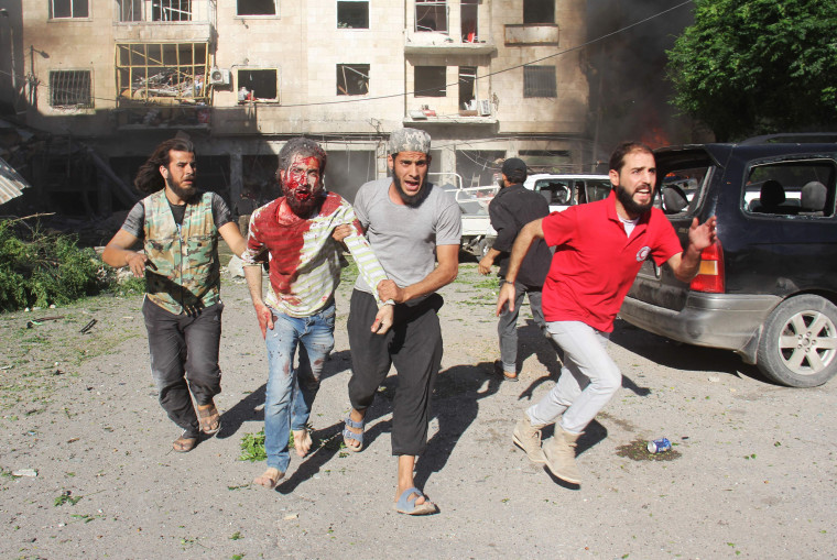 Image: Syrians help an injured man following reported airstrikes in Idlib