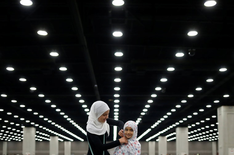 Image: Salma adjusts the headscarf of her sister Layla ahead of the jenazah for Muhammad Ali in Louisville
