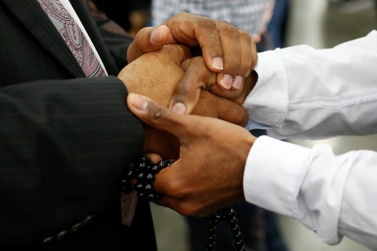 Image: Men hold hands ahead of funeral prayer for Muhammad Ali in Louisville