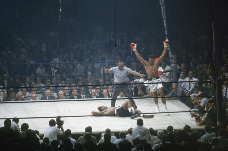 Muhammad Ali raises his arms in celebrations after putting down Sonny Liston in the canvas as referee Jersey Joe Walcott gives count in the first round of the World Heavyweight Title bout at St. Dominic's Hall on May 25, 1965 in Lewiston, Maine.
