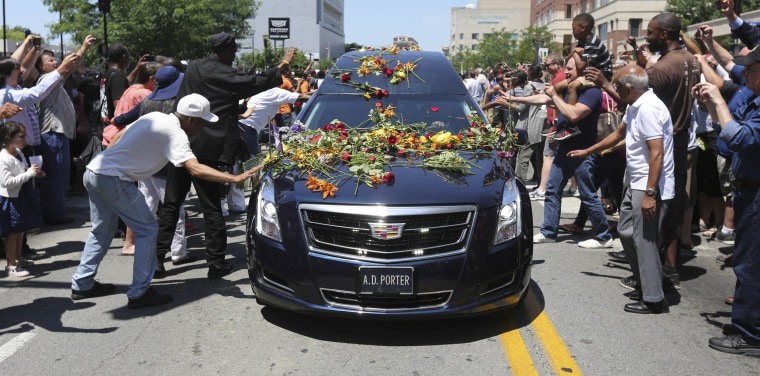 Image: Fans reach out to touch the hearse carrying the body of Muhammad Ali with flowers as it drives down Broadway toward Cave Hill Cemetery in Louisville