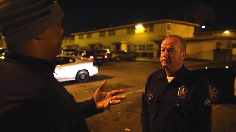 Watts Gang Task Force member Donny Joubert talks to LAPD Officer John Coughlin at the scene of a boy's arrest.