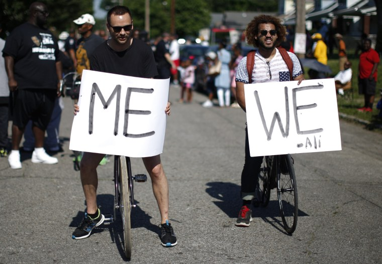 Image: Mourners hold signs during funeral procession for three-time heavyweight boxing champion Muhammad Ali in Louisville