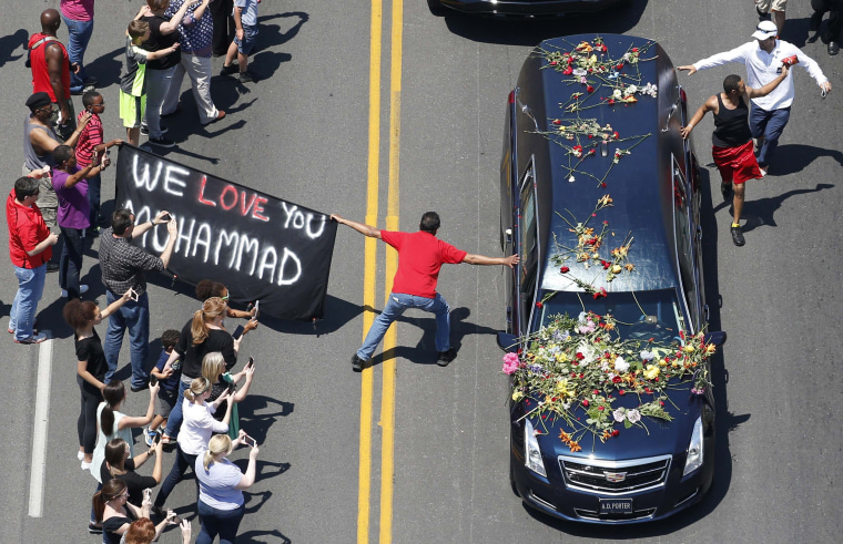 Image: Well-wishers touch the hearse carrying the remains of Muhammad Ali during the funeral procession in Louisville