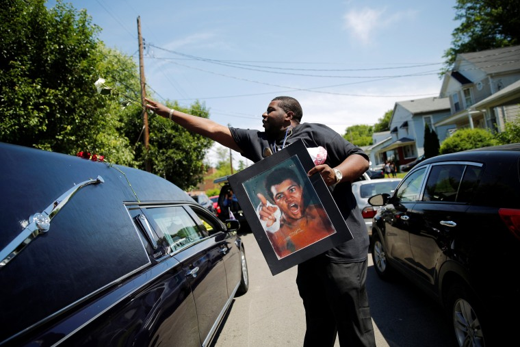 Image: A man throws a rose over the hearse carrying the remains of Muhammad Ali during the funeral procession for the three-time heavyweight boxing champion in Louisville, Kentucky, U.S.