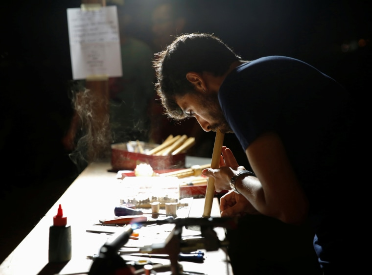 Image: An artisan makes a Maltese traditional wind instrument at an artisans' market during the Ghanafest folk music festival in Floriana