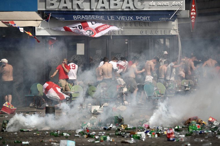 Image: England fans react after police sprayed tear gas during clashes