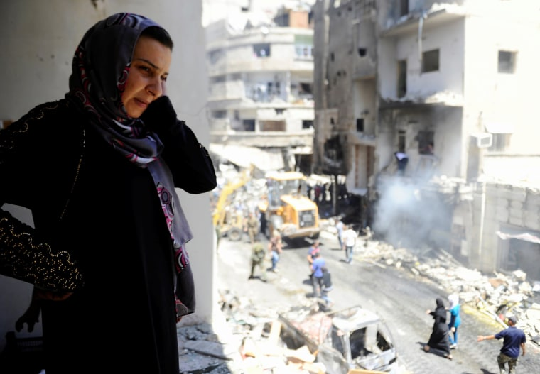Image: A woman inspects a damaged site after a suicide and car bomb attack in south Damascus Shi'ite suburb of Sayeda Zeinab