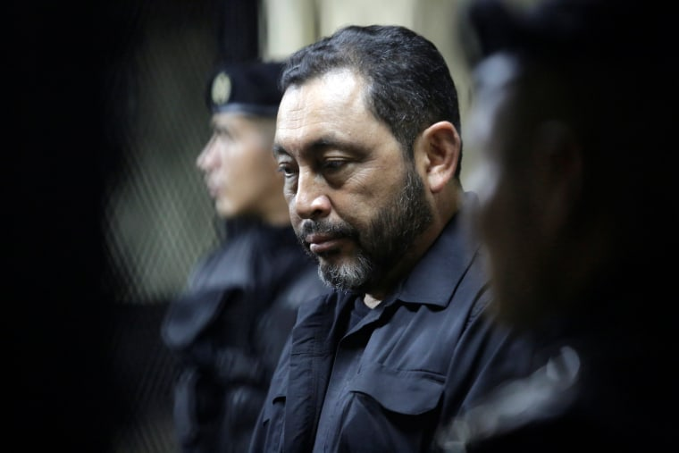 Image: Guatemala's former Interior Minister, Mauricio Lopez Bonilla is escorted by policemen at the basement of the Supreme Court of Justice after being arrested for having links to a corruption scandal led by former president Perez Molina, in Guatemala C