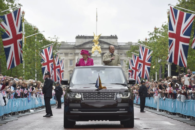 Image: Britain's Queen Elizabeth and Prince Philip wave to guests attending the Patron's Lunch on the Mall, an event to mark her 90th birthday, in London