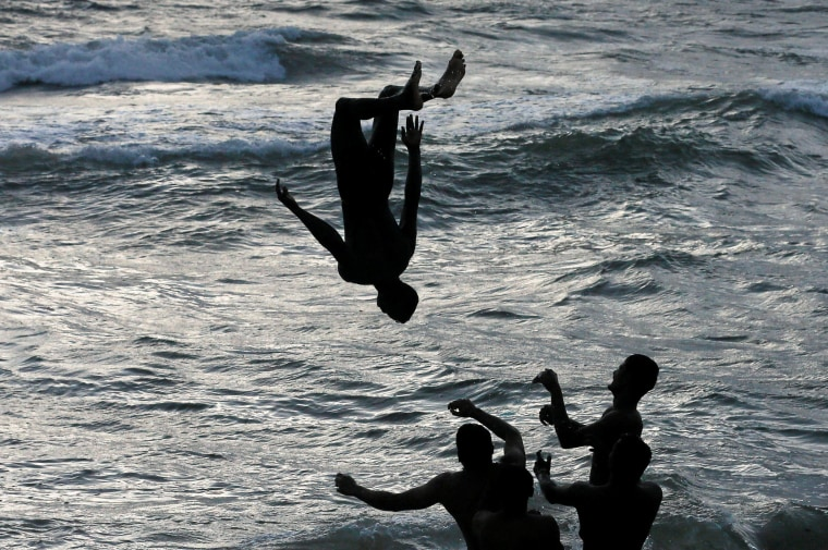 Image: A man is flipped into water by others at a beach in Colombo