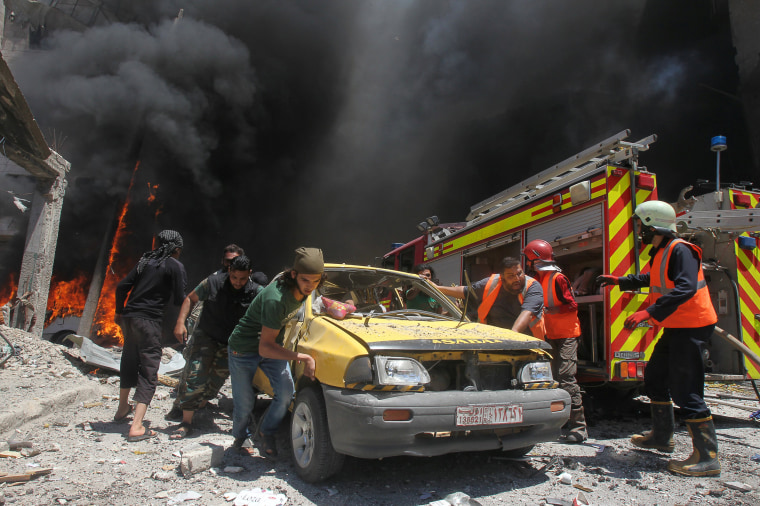 Image: Civil defence members and rescuers push a car at a site hit by air strikes in Idlib city