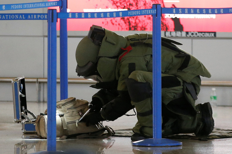 Image: A bomb disposal expert checks a luggage near the site of a blast at a terminal in Shanghai's Pudong International Airport