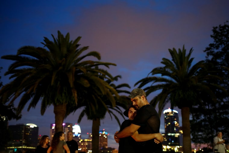 Image: Partners embrace during vigil to commerate victims of a gay night club shooting in Orlando, Florida