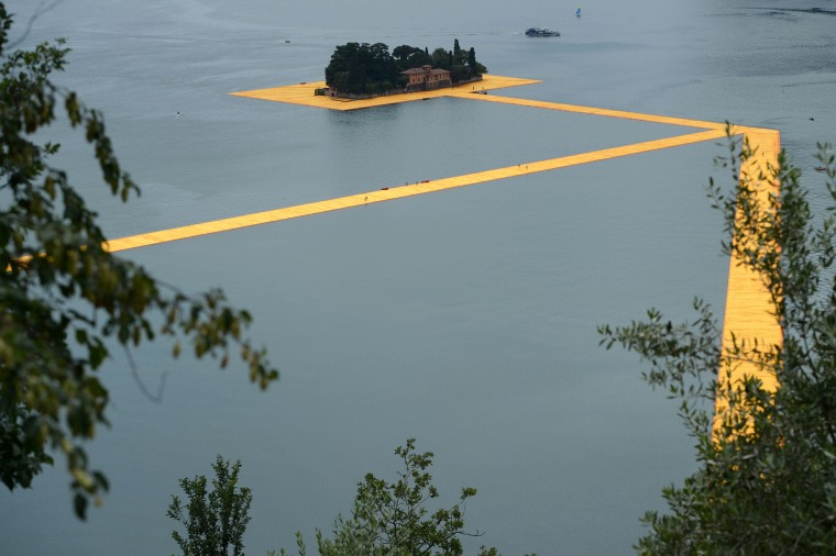 """A picture shows a partial view of the monumental installation \""""The Floating Piers\"""" created by artist Christo Vladimirov Javacheff and Jeanne-Claude, on June 16, 2016 during a press preview at the lake Iseo, northern Italy. Some 200,000 floating cubes create a 3-kilometers runway connecting the village of Sulzano to the small island of Monte Isola on the Iseo Lake for a 16-day outdoor installation opening on June 18. / AFP PHOTO / Filippo MONTEFORTEFILIPPO MONTEFORTE/AFP/Getty Images"""