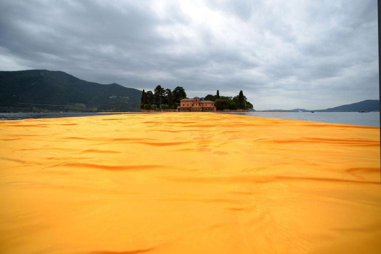 "A picture shows the monumental installation ""The Floating Piers"" created by Artist Christo Vladimirov Javacheff and Jeanne-Claude, on June 16, 2016 during a press preview at the lake Iseo, northern Italy. Some 200,000 floating cubes create a 3-kilometers runway connecting the village of Sulzano to the small island of Monte Isola on the Iseo Lake for a 16-day outdoor installation opening on June 18. / AFP PHOTO/AFP/Getty Images"