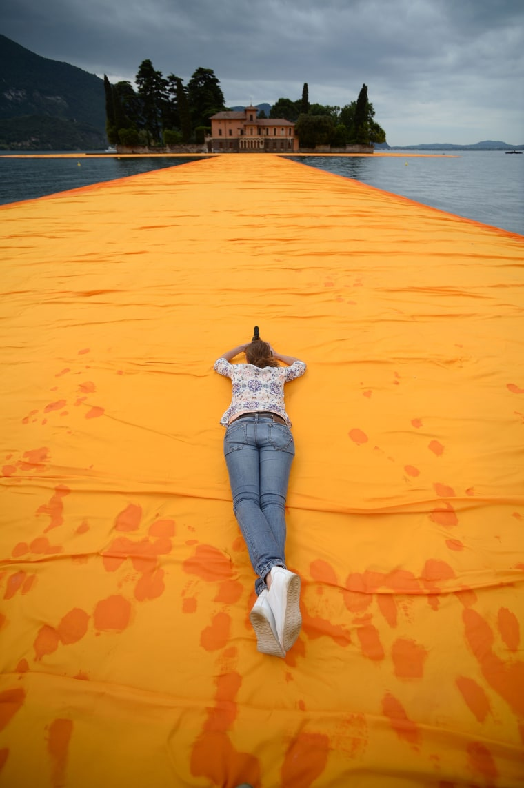 """A woman takes pictures of the monumental installation \""""The Floating Piers\"""" created by Artist Christo Vladimirov Javacheff and Jeanne-Claude, on June 16, 2016 during a press preview at the lake Iseo, northern Italy. Some 200,000 floating cubes create a 3-kilometers runway connecting the village of Sulzano to the small island of Monte Isola on the Iseo Lake for a 16-day outdoor installation opening on June 18. / AFP PHOTO/AFP/Getty Images"""