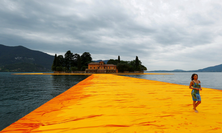 A woman walks on the installation 'The Floating Piers' by Bulgarian-born artist Christo Vladimirov Yavachev known as Christo, on the Lake Iseo, northern Italy, June 16, 2016.REUTERS/Stefano Rellandini