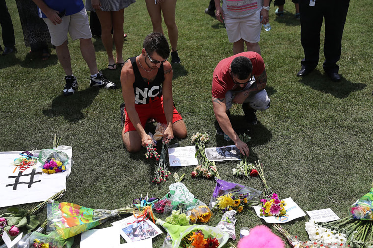 Chris Drozd, and Stefan Salvatore (L-R) lay flowers down as they visit a memorial at the Dr. Phillips Center for the Performing Arts for the victims of the Pulse gay nightclub shooting where Omar Mateen allegedly killed 50 people on June 13, 2016 in Orlando, Florida. The mass shooting killed at least 49 people and injuring 53 others in what is the deadliest mass shooting in the country??s history.