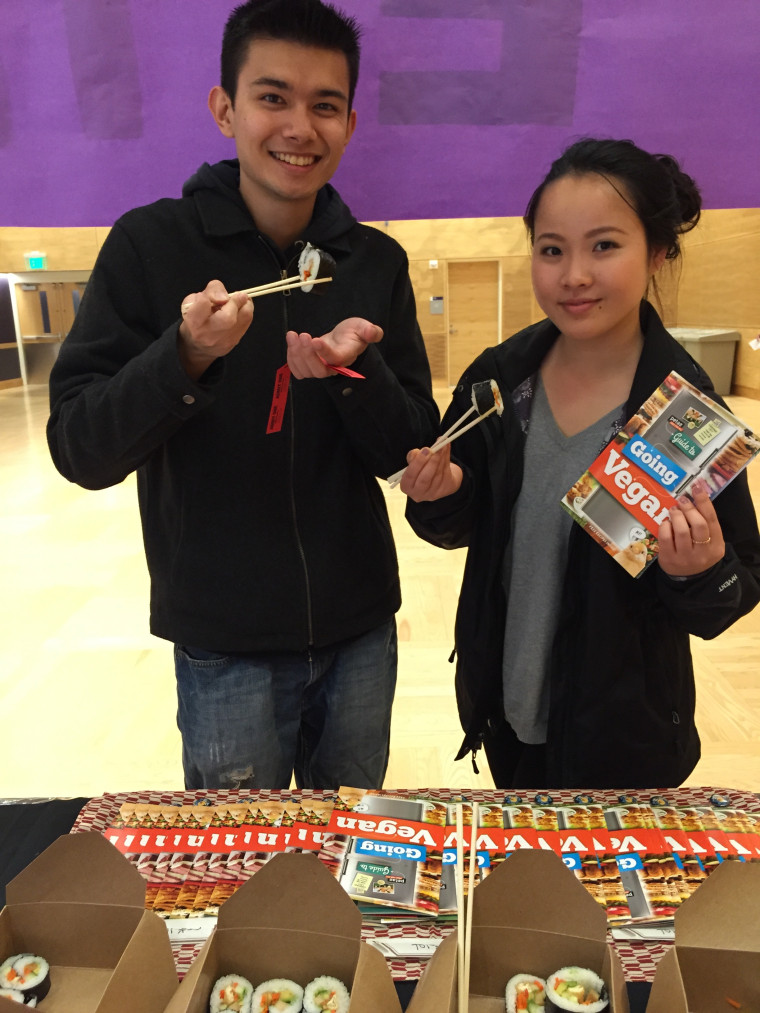 Students eating vegan sushi from a peta2 table.